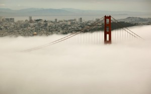 The skyline of San Francisco and the south tower of the Golden Gate Bridge are seen from the Marin Headlands as they rise above the fog in Sausalito, California March 21, 2012. A celebration held over the Memorial Day weekend in May will commemorate the bridge's 75th anniversary this year. REUTERS/Robert Galbraith (UNITED STATES - Tags: ANNIVERSARY CITYSPACE SOCIETY) - RTR2ZOWD